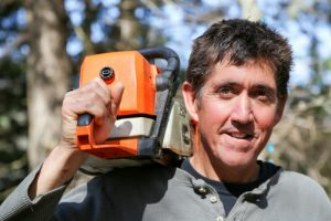 man with chain saw on his shoulder